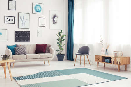 Blue carpet and wooden cupboard in living room interior with gallery of posters above beige couch