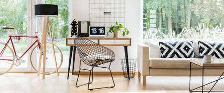 Patterned pillows on beige settee next to desk with laptop and plant in freelancers room with bike, metal chair and lamp