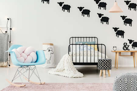 Bright kid bedroom interior with sheep motif decorations on the wall and metal bed