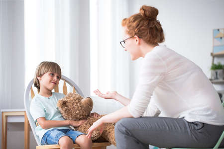 Mother talking to her polite, young son hugging a teddy bear Stock Photo