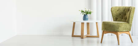 Pear green armchair standing next to a wooden table with white roses in simple living room interior
