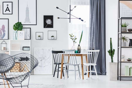Modern, designer lamp hanging above wooden table in white dining room interior