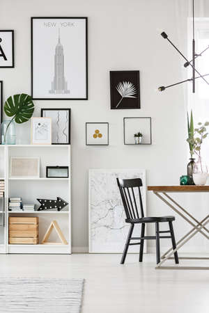 Simple gallery on white wall in dining room interior with plants Stock Photo