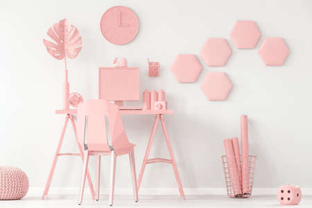 Pastel pink and white home office interior with decorative honeycomb on the wall and computer on the desk Stock Photo