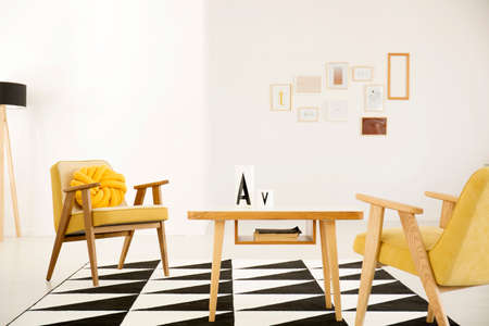 Warm, yellow living room interior with knot cushion on vintage armchair  standing next to a wooden table