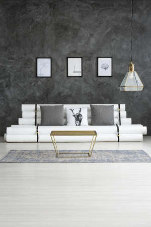 Gold table on grey carpet near sofa in cozy living room interior with posters on concrete wall