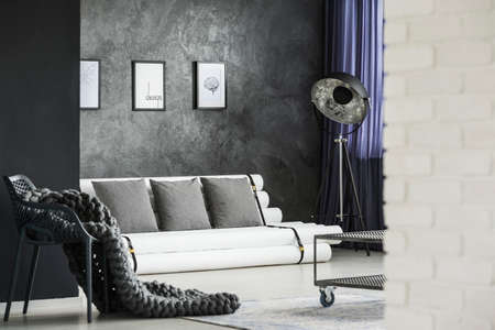 Knit blanket on chair and grey cushions on settee in modern living room interior with posters