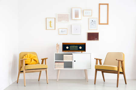 Vintage yellow armchairs and white cupboard with radio in bright living room interior