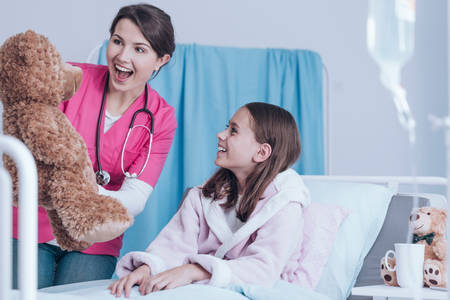 Young nurse in pink uniform holding a teddy bear and having fun with a little patient Stock Photo
