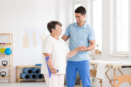 Disabled elderly woman with endoprosthesis and smiling physiotherapist in rehabilitation center Stock Photo