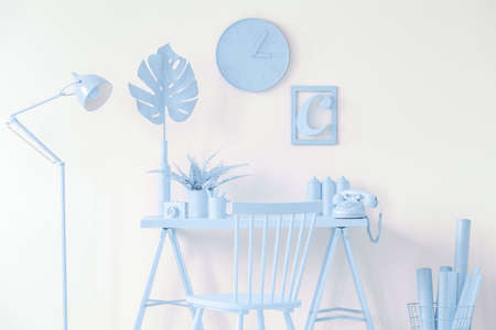 Oldschool phone placed on light blue desk with plants standing in white room interior