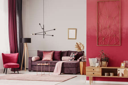 Wooden cupboard and red armchair in cozy living room interior with mockup of empty poster