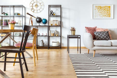 Multifunctional flat interior with gold poster above beige sofa and black chair at a wooden dining table