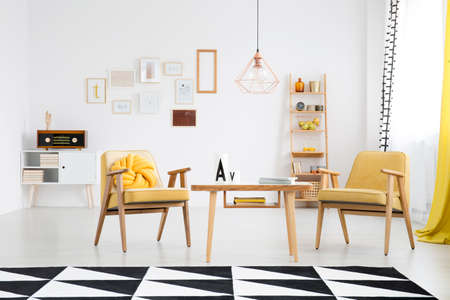 Bright living room interior with retro armchairs next to a wooden table and carpet with geometric pattern