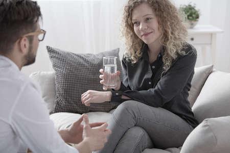 Sourire femme buvant de l & # 39 ; eau lors d & # 39 ; une réunion avec un vieux ami Banque d'images - 97184412
