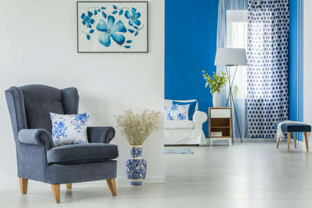 Flowers in decorative vase next to a blue armchair with cushion against white wall with poster in open space interior Stock Photo