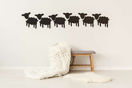 Big, handmade, woolen blanket thrown on a grey bench standing under decorative paper sheep on the wall in simple interior Stock Photo