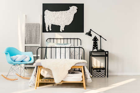 Simple, handmade sheep poster hanging on white wall above bed in bright kid bedroom interior
