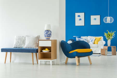 Lamp on wooden cabinet between a stool with cushions and a blue armchair in modern living room interior