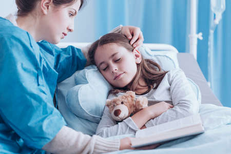 Worried mother holding a book and watching over a little girl sleeping at the hospital and hugging teddy bear