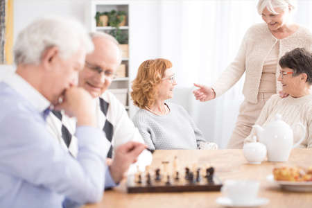 A group of seniors spending time together talking and playing chess