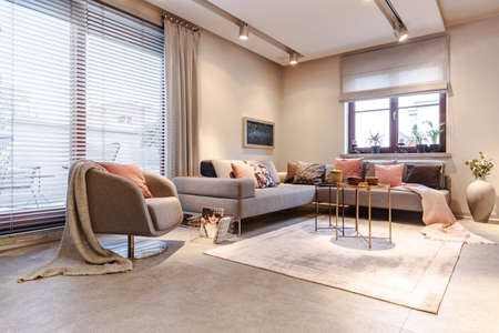 Gold table on carpet near grey armchair with blanket in spacious apartment interior with corner couch
