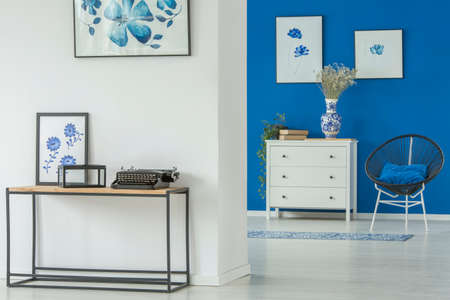 Typewriter on the table and armchair next to a white cupboard in apartment interior with blue floral posters