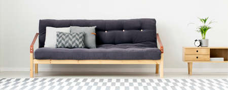 Black settee with grey cushions next to wooden cupboard with plant and clock in bright living room interior with patterned carpet