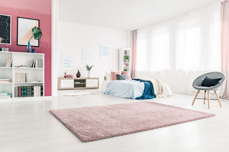 Pink carpet and grey armchair in pastel open space interior with blue bedding on the bed