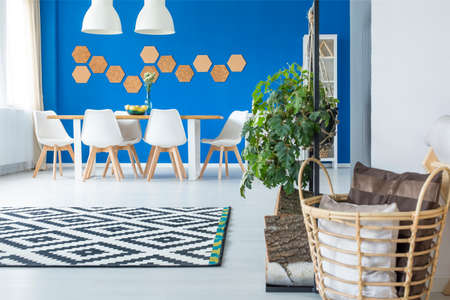 Basket with cushions and patterned carpet in spacious blue dining room interior with white chairs at wooden table Stock Photo