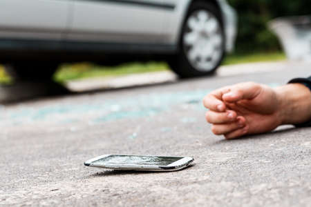 Careless person hit by a car after crossing the road while talking on the phone Фото со стока