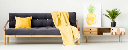 Yellow pillow and blanket on black settee next to rustic cupboard with pineapple poster and plant in living room interior Stock Photo