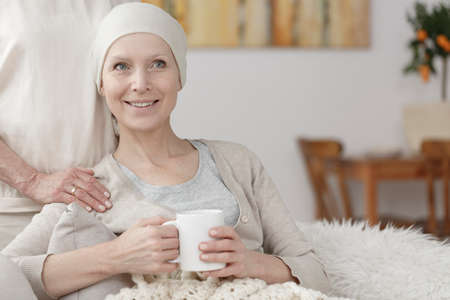 Smiling lady with cancer wearing a headscarf sitting on a sofa with white tea mug Stock Photo