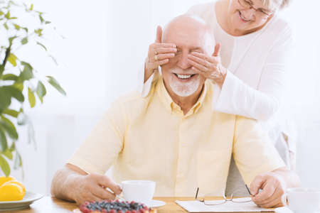 Wife covering smiling senior man's eyes as a birthday surprise Archivio Fotografico - 97184705