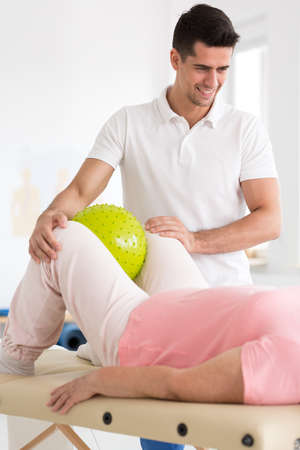 Smiling physiotherapist supporting patient squeezing yellow ball between knees