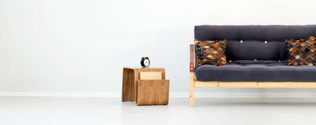 Clock on wooden designer table next to black sofa with brown patterned pillows against the wall with copy space in flat interior