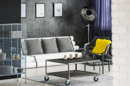 Dark living room interior with industrial recycled furniture - metal racks, coffee table on wheels, chair, floor lamp and a sofa made of paper tubes