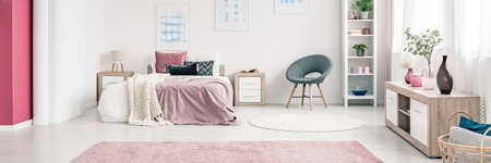Grey armchair next to a bed with pink bedsheets in womans bedroom interior with wooden cupboard