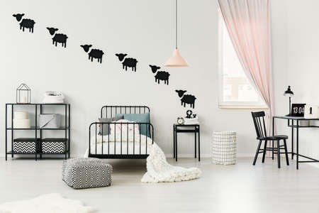 Bright, cozy child bedroom interior with window, metal bed and sheep wallpaper