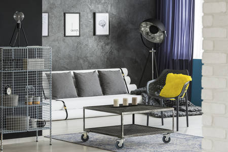 Monochromatic sitting room interior with industrial, designer furniture, paper tubes couch and colorful elements