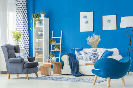 White sofa with floral cushions and two navy blue armchairs in bright living room interior Stock Photo