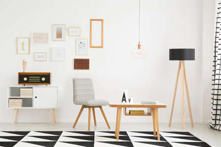 Wooden lamp, gray chair and carpet with geometric pattern in cozy living room interior with copper lamp Stock Photo