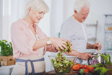 Older woman tossing a salad and her husband stirring food in a pot, cooking together Reklamní fotografie - 97751936