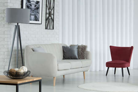 Dark armchair next to couch in living room interior with grey lamp, poster and plastic tubes Stock Photo