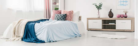 Pink pillows and blue bedsheets on bed in pastel bedroom interior with rug and wooden cupboard