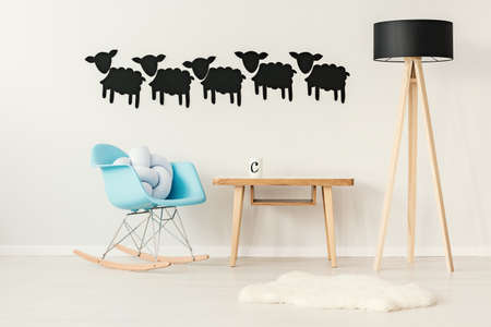 Blue rocking chair with a pillow standing by a wooden table with a mug on it in sheep theme flat interior Stock Photo