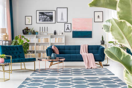 Copper table near navy blue sofa and armchair in sophisticated living room interior with posters Stock Photo