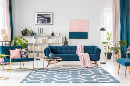 Patterned carpet in pink and blue living room interior with sofa against white wall with painting Banco de Imagens - 97321020