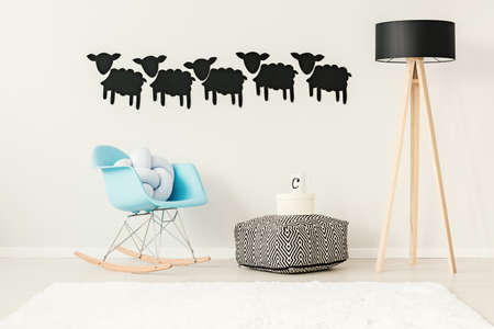 Patterned pouf with a round box and mug standing between a rocking chair and a big wooden lamp in apartment interior Stock Photo
