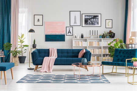 Round table on patterned carpet in pastel living room interior with blue settee and gallery of posters Stock Photo